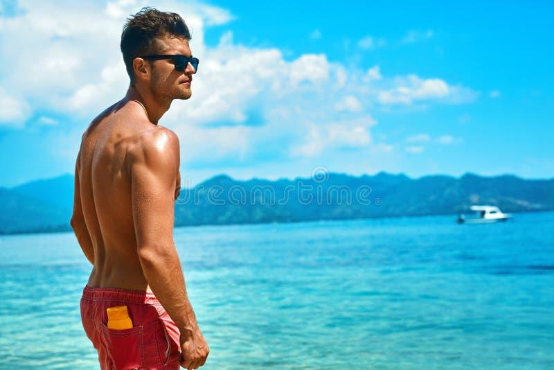 Hombre atractivo que broncea con crema de piel de Sunblock en la playa del verano imagenes de archivo