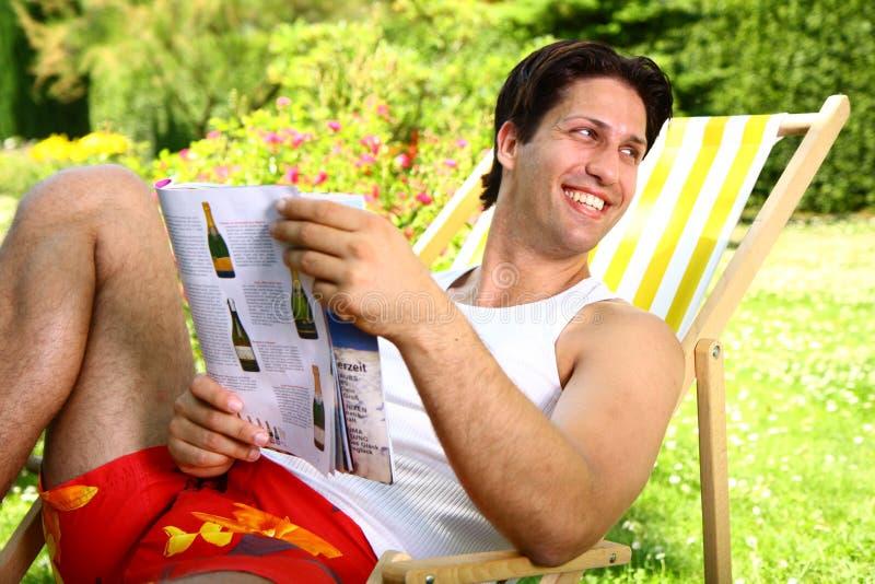 Hombre atractivo que disfruta del día soleado que sostiene una revista imágenes de archivo libres de regalías