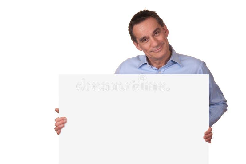 Hombre atractivo que lleva a cabo la muestra blanca en blanco fotos de archivo libres de regalías
