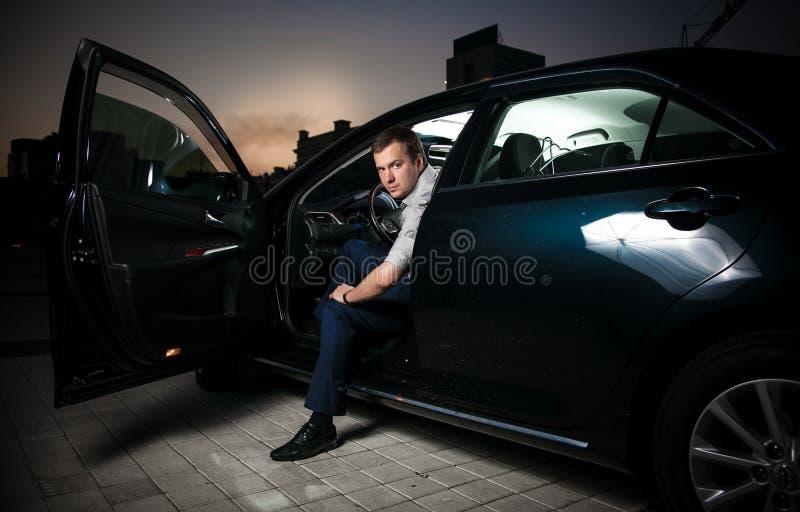 Hombre atractivo que se sienta en coche foto de archivo
