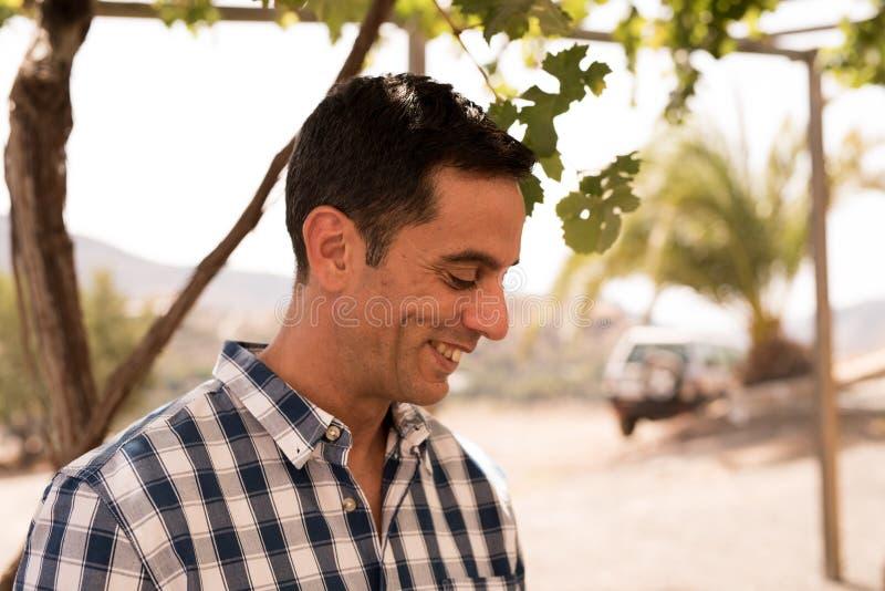 Hombre atractivo que sonríe en la sol en un vineya foto de archivo libre de regalías