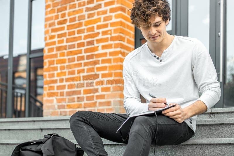 Hombre atractivo que sostiene la libreta en sus manos y que se sienta en pasos concretos fotos de archivo