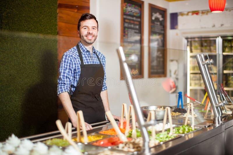 Hombre atractivo que trabaja en un bufete de ensaladas fotos de archivo