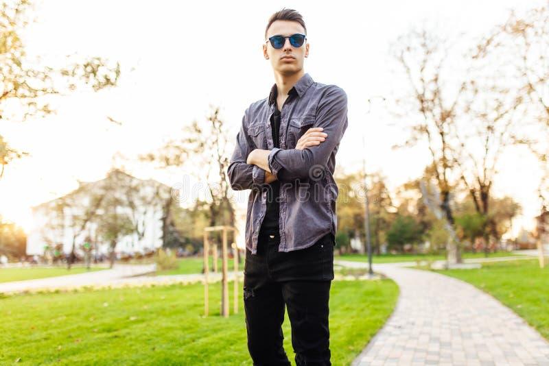 Hombre atractivo vestido en la ropa elegante, gafas de sol, paseos adentro fotos de archivo