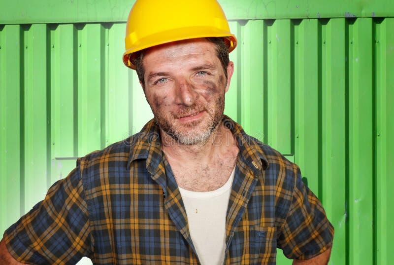 Hombre atractivo y confiado joven del trabajador del contratista o de construcción con el casco de seguridad del constructor que  foto de archivo