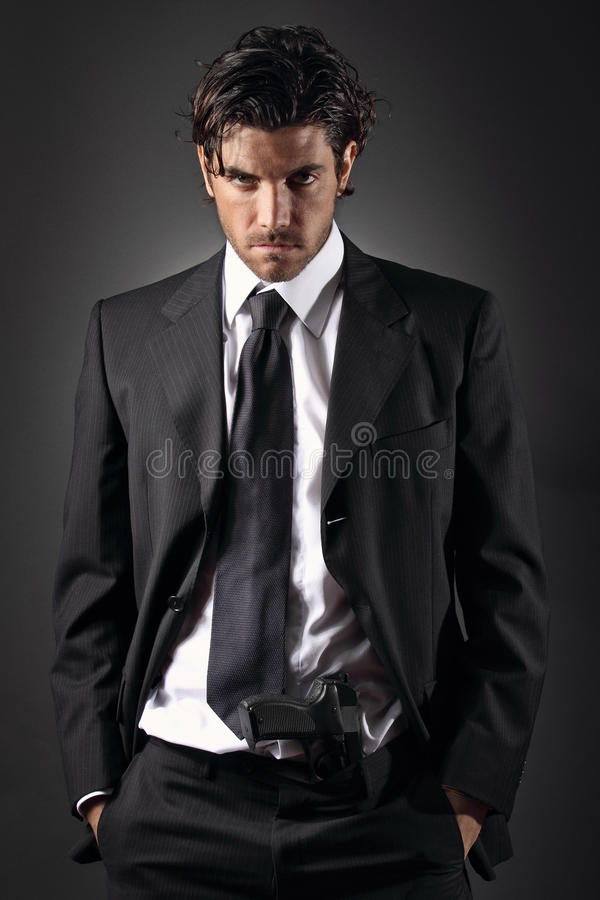 Hombre atractivo y elegante que presenta con un arma en sus pantalones imagen de archivo