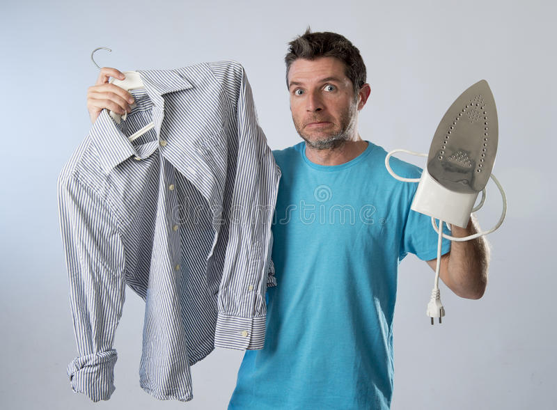 Hombre atractivo y frustrado joven que sostiene el hierro y la camisa subrayados y cansados en cara agujereada y perezosa foto de archivo libre de regalías