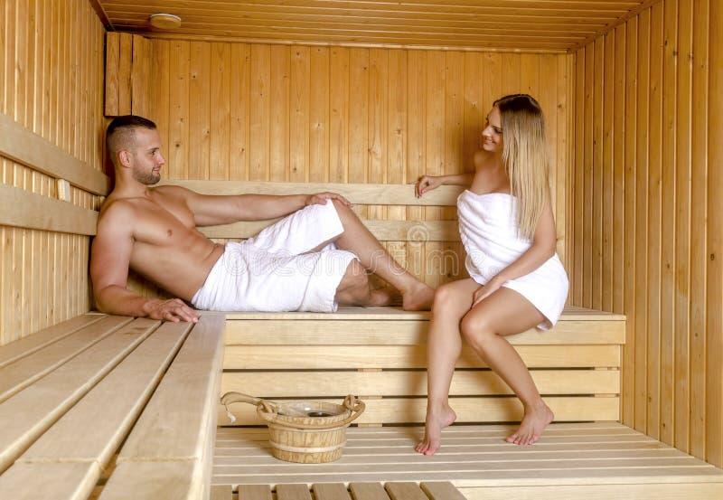 Hombre atractivo y mujer hermosa que se relajan junto en sauna fotografía de archivo