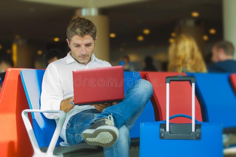 Hombre atractivo y relajado joven del viajero con el equipaje que trabaja con vuelo que espera del ordenador portátil para en el  fotos de archivo libres de regalías
