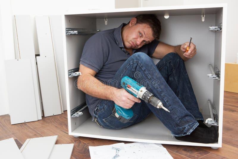 Hombre atrapado mientras que ensambla los muebles del paquete plano imagen de archivo libre de regalías