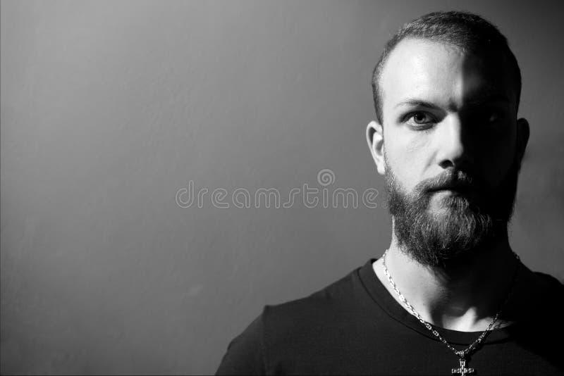 Hombre audaz fuerte fresco que mira la cámara blanco y negro imagen de archivo