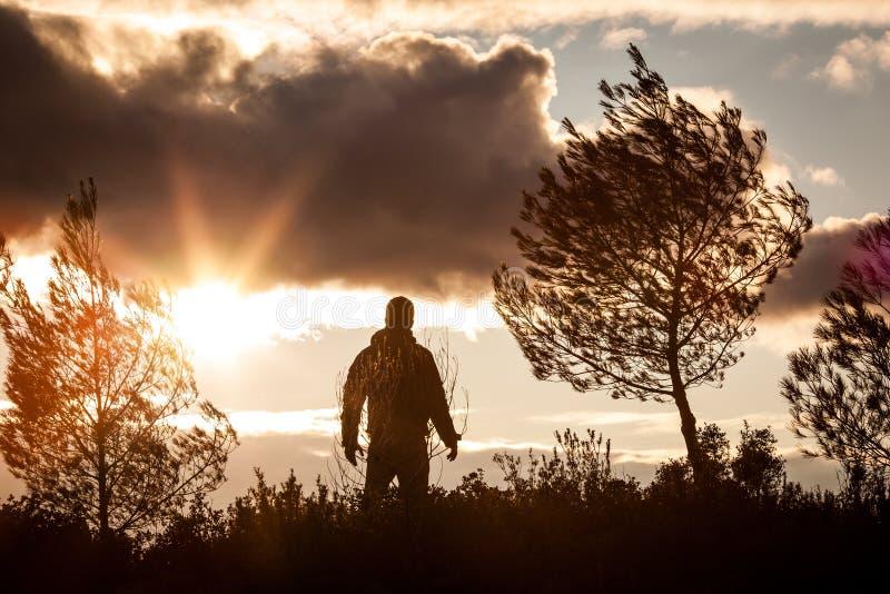 Hombre aventurero observando una puesta del sol preciosa en la naturaleza, solo, stan foto de archivo libre de regalías