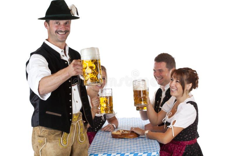 Hombre bávaro con la cerveza de Oktoberfest de las bebidas de los amigos foto de archivo
