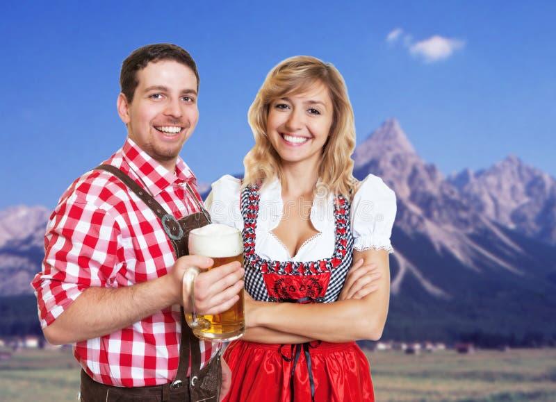 Hombre bávaro con los pantalones de cuero y la mujer rubia con el dirndl cel imagen de archivo libre de regalías