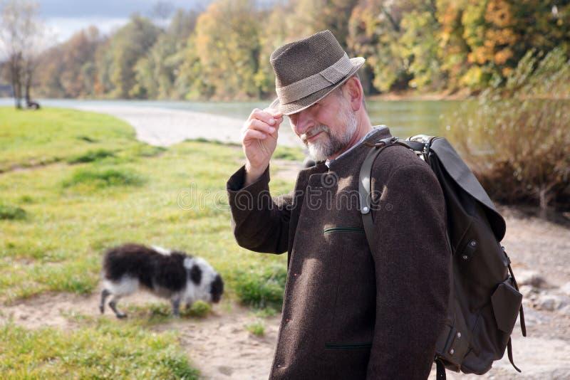Hombre bávaro por el río con su perro imagenes de archivo