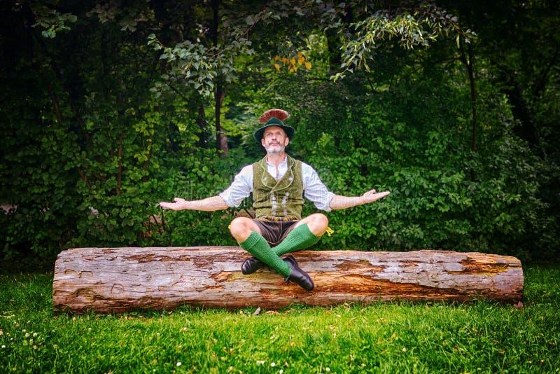 Hombre bávaro que se sienta en tocón y meditar de árbol imagen de archivo libre de regalías