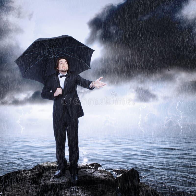 Hombre bajo el paraguas que controla para saber si hay lluvia imagen de archivo