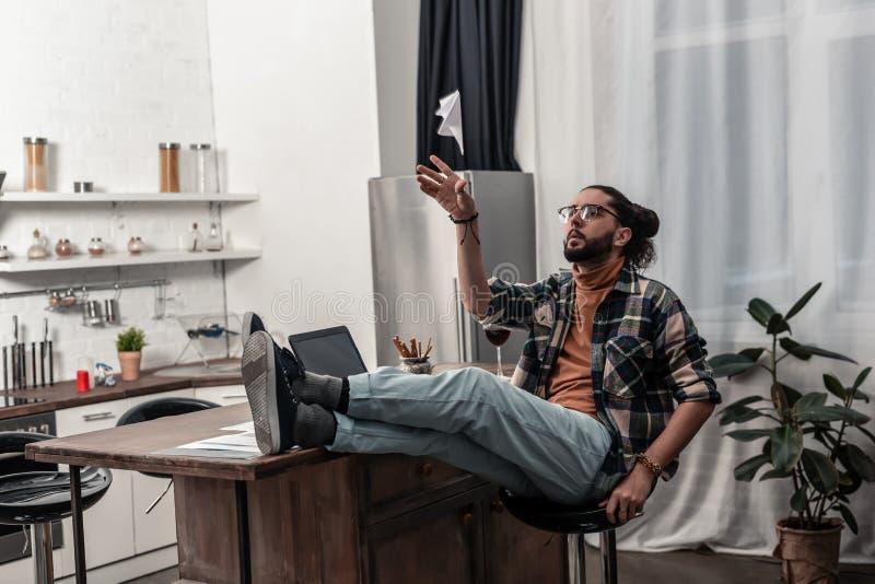 Hombre barbudo agradable que juega con un avión de papel fotografía de archivo