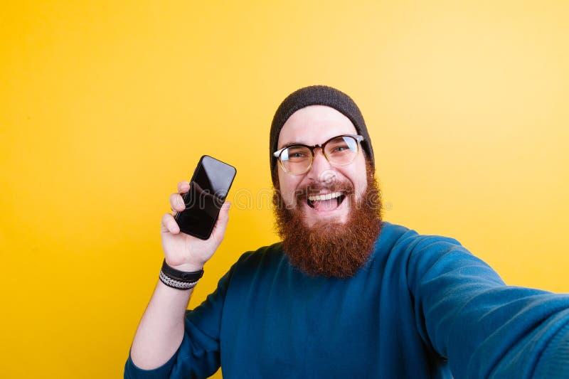 Hombre barbudo alegre del inconformista que muestra smartphone imagen de archivo libre de regalías