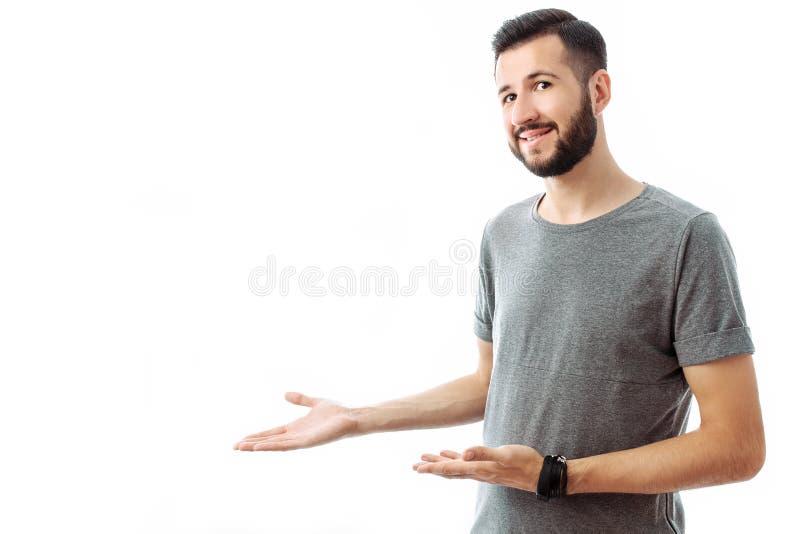 Hombre barbudo alegre joven que señala el finger en el espacio vacío en el CCB foto de archivo libre de regalías