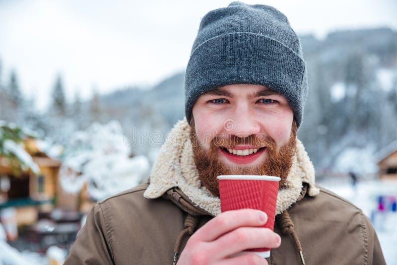Hombre barbudo alegre que bebe el café caliente al aire libre en invierno imagenes de archivo