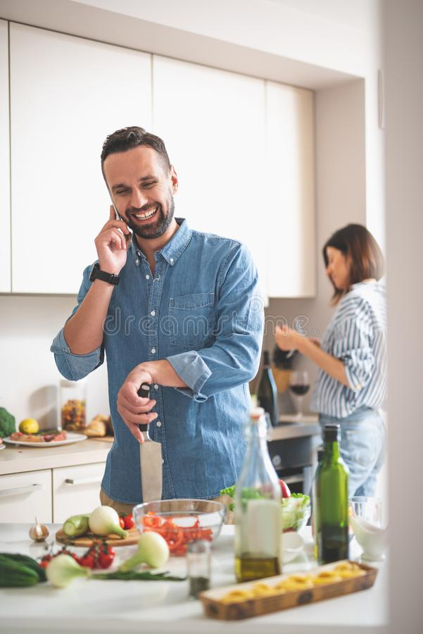 Hombre barbudo alegre que habla en el teléfono móvil en cocina imágenes de archivo libres de regalías