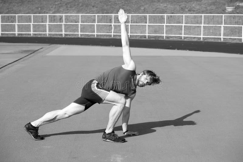 Hombre barbudo atlético con el cuerpo muscular que hace ejercicios imagenes de archivo