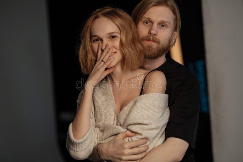 Hombre barbudo atractivo con el pelo marrón largo que abraza a su novia sonriente positiva imagen de archivo libre de regalías