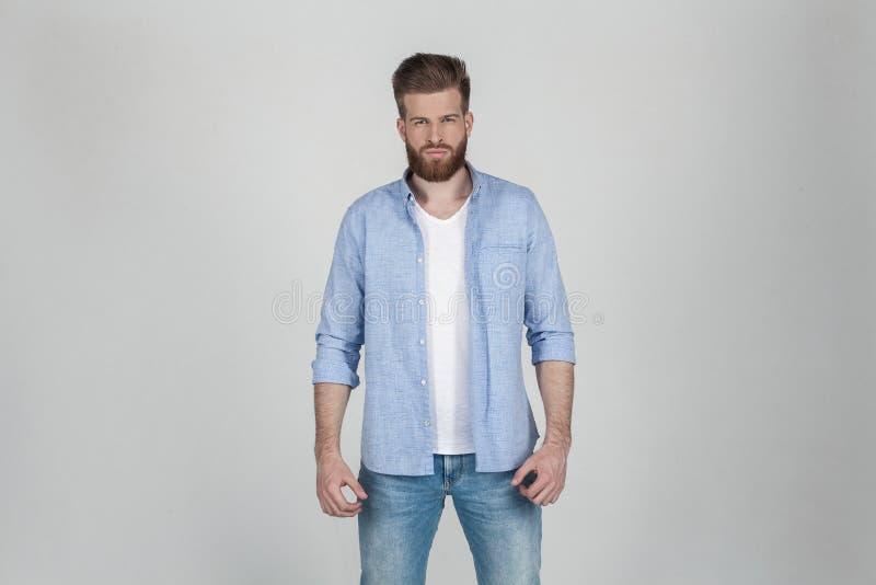 Hombre barbudo atractivo hermoso vestido en ropa casual que él se coloca delante de un fondo blanco fotografía de archivo libre de regalías