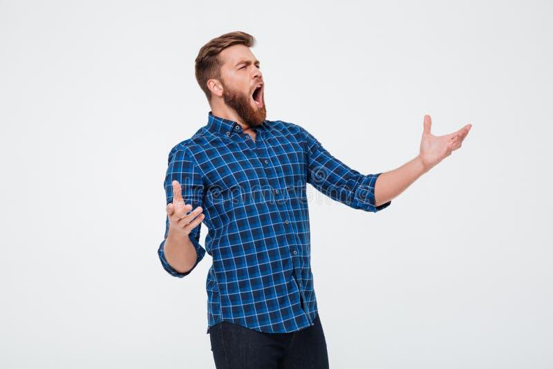 Hombre barbudo atractivo joven que canta ruidosamente fotos de archivo