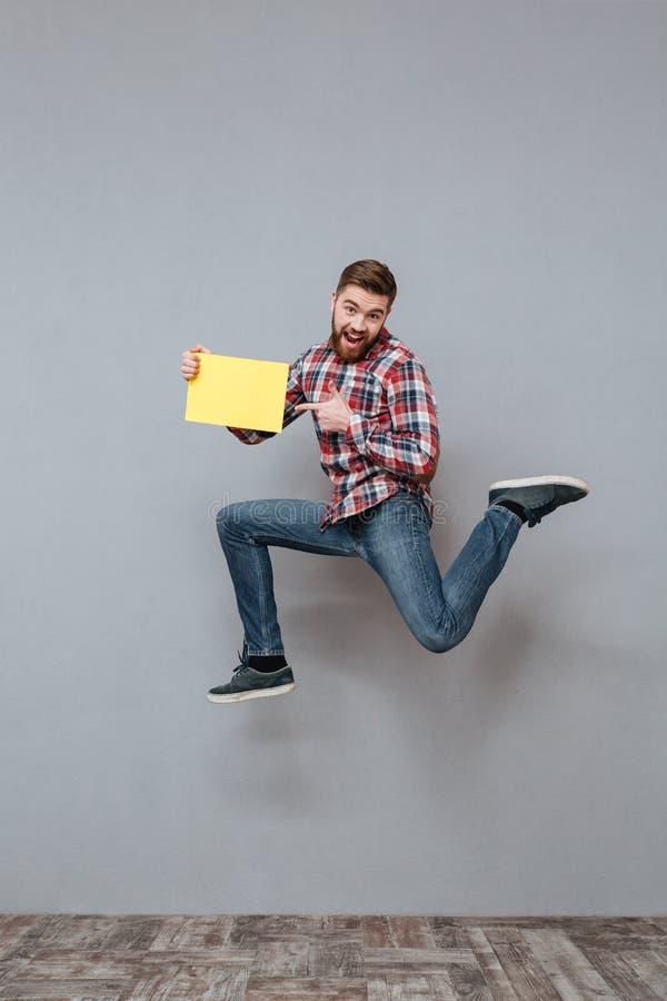 Hombre barbudo atractivo que celebra el salto en blanco del copyspace fotos de archivo libres de regalías