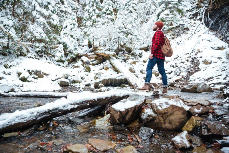 Hombre barbudo atractivo que se coloca cerca del río en bosque del invierno fotografía de archivo