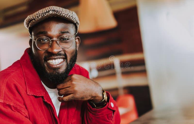 Hombre barbudo atractivo que sonríe mientras que se sienta solamente y mírale imagen de archivo libre de regalías