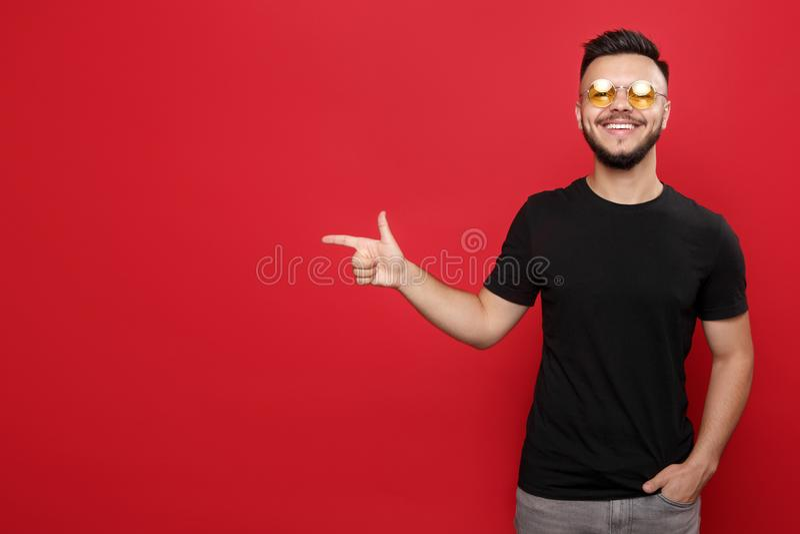 Hombre barbudo brillante en gafas de sol amarillas y camiseta negra que señala lejos la risa en fondo rojo fotos de archivo
