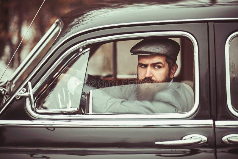 Hombre barbudo brutal con un bigote adentro con el pelo oscuro y la barba larga en coche retro imagen de archivo
