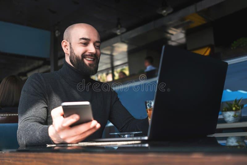 Hombre barbudo calvo en el funcionamiento negro del cuello alto en el ordenador port?til, sosteniendo smartphone mientras que se  foto de archivo libre de regalías