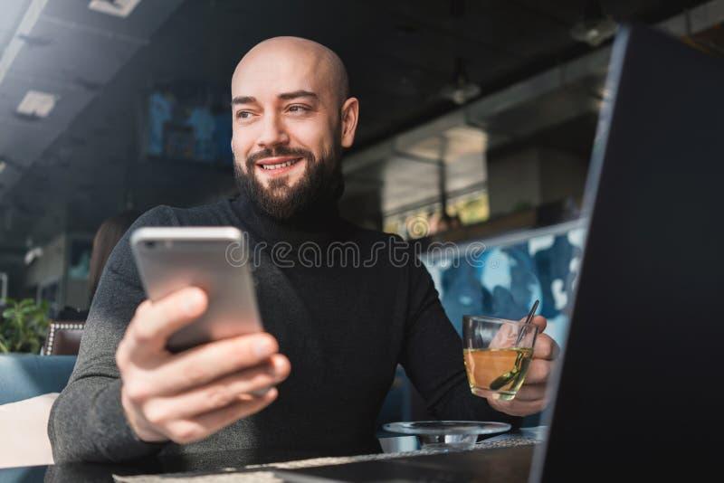 Hombre barbudo calvo en el funcionamiento negro del cuello alto en el ordenador port?til, sosteniendo smartphone mientras que se  imagen de archivo libre de regalías