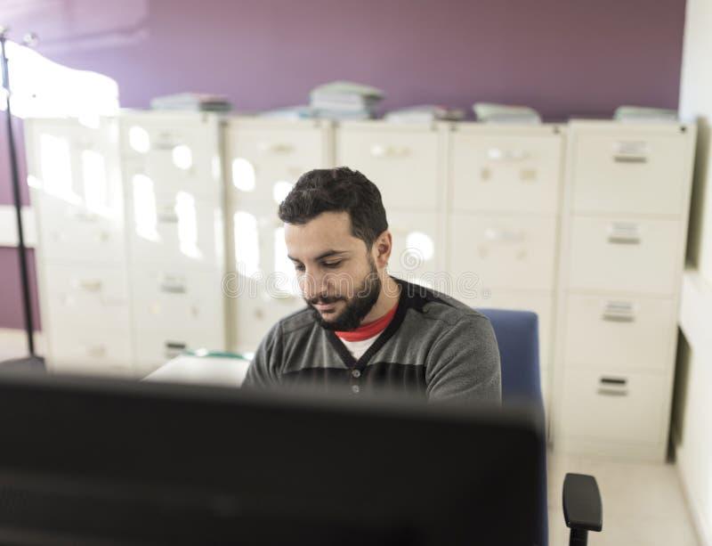 Hombre barbudo casual que trabaja en la oficina imagen de archivo libre de regalías