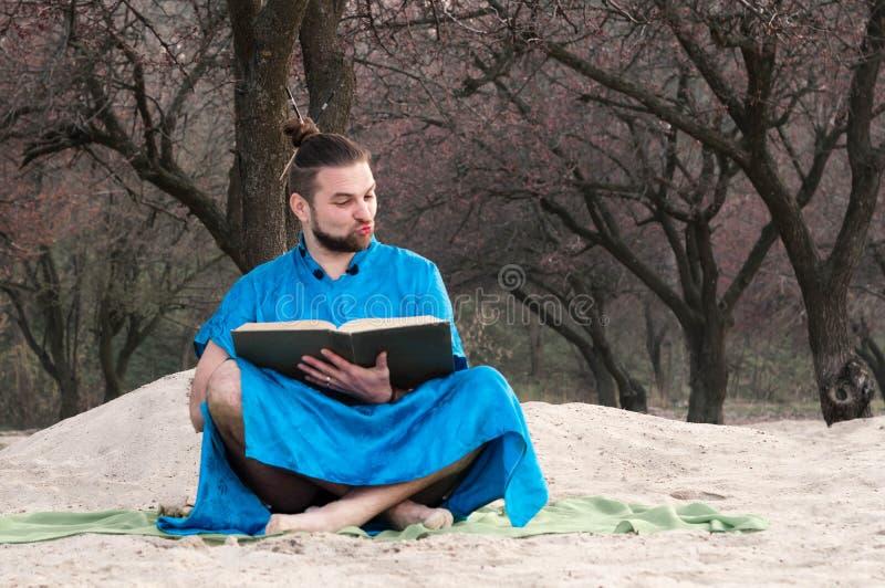Hombre barbudo chocado en kimono azul con el bollo en la cabeza y componer sentarse, mirando el libro grande imagen de archivo libre de regalías