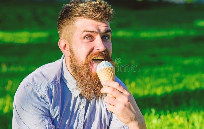 Hombre barbudo con el cono de helado El hombre con la barba y el bigote en cara feliz lame el helado, hierba en fondo imágenes de archivo libres de regalías