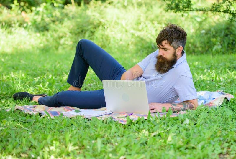 Hombre barbudo con el fondo de relajación de la naturaleza del prado del ordenador portátil Escritor que busca el ambiente de la  imágenes de archivo libres de regalías