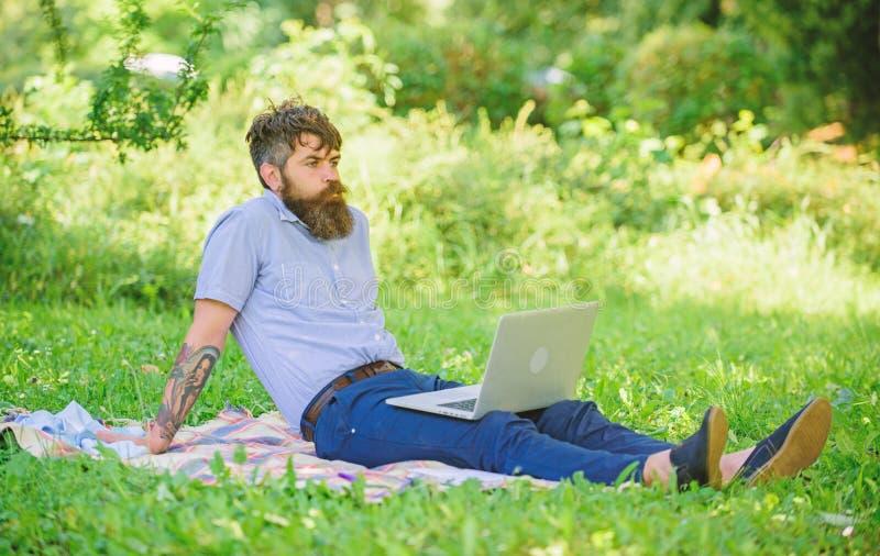 Hombre barbudo con el fondo de relajaci?n de la naturaleza del prado del ordenador port?til Blogger inspirador por naturaleza El  fotografía de archivo