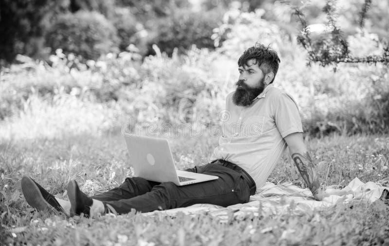 Hombre barbudo con el fondo de relajaci?n de la naturaleza del prado del ordenador port?til Blogger inspirador por naturaleza El  fotografía de archivo libre de regalías