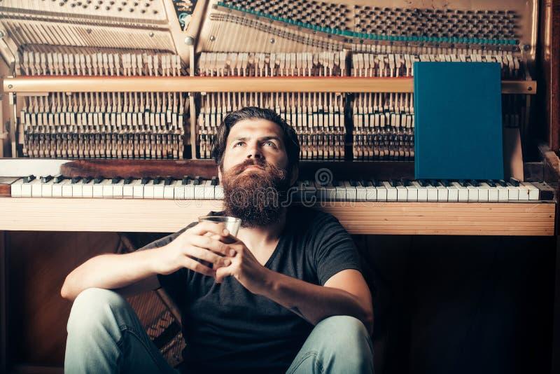 Hombre barbudo con el piano de madera cercano de cristal foto de archivo libre de regalías