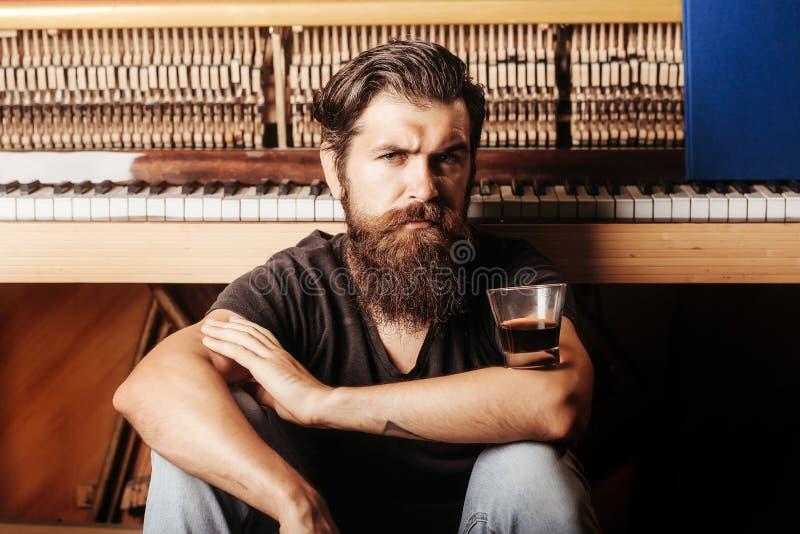 Hombre barbudo con el piano de madera cercano de cristal fotos de archivo