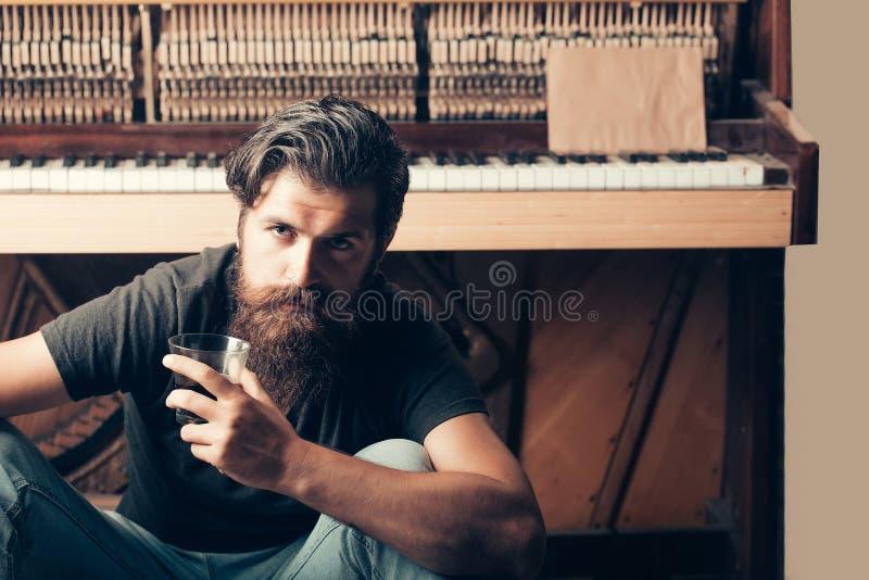 Hombre barbudo con el piano de madera cercano de cristal fotografía de archivo