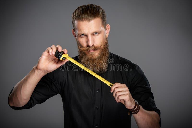 Hombre barbudo con la cinta de la medida fotos de archivo