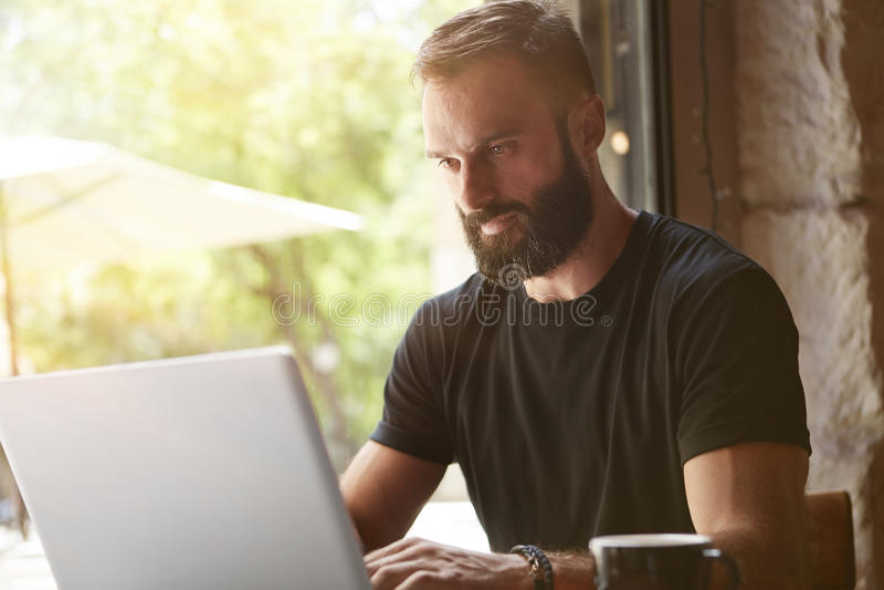 Hombre barbudo concentrado que lleva el café urbano de trabajo de la tabla de madera del ordenador portátil de la camiseta negra  foto de archivo