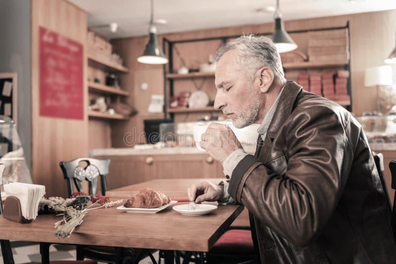 Hombre barbudo concentrado que siente el aroma del café fotos de archivo