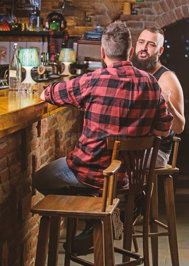 Hombre barbudo del inconformista pasar ocio con el amigo en el contador de la barra Bebidas fuertes del alcohol Horas de apertura imagen de archivo